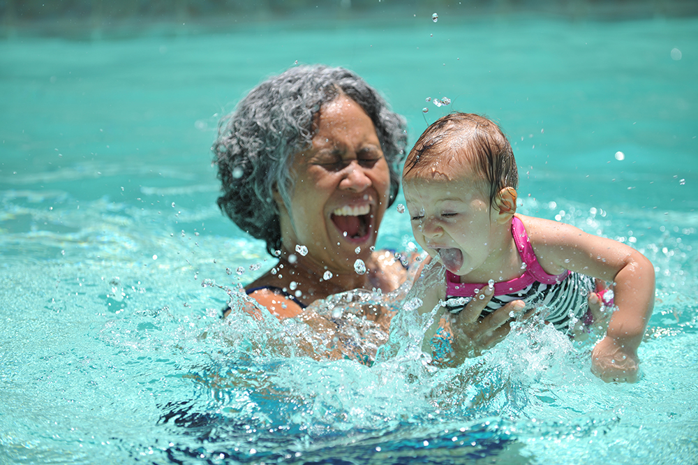 grandmother splashing in a pool with grandchild.