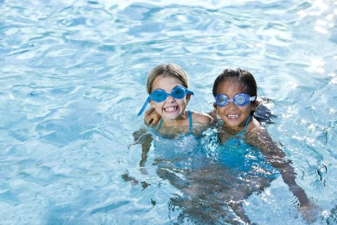 Two girls wearing swim goggles playing together in swimming pool.