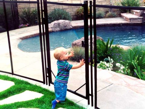 little boy in front of gate by the pool