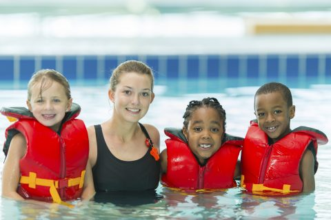 3 kids in life jacketswith swimming instructor