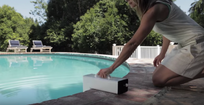 woman kneeling installing a pool alarm.