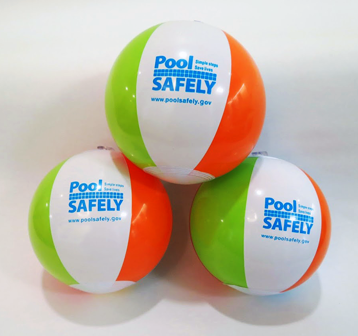 three green orange and white beach balls with the pool safely logo.