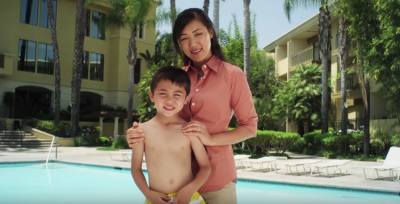 a woman and child standing next to a pool smiling.