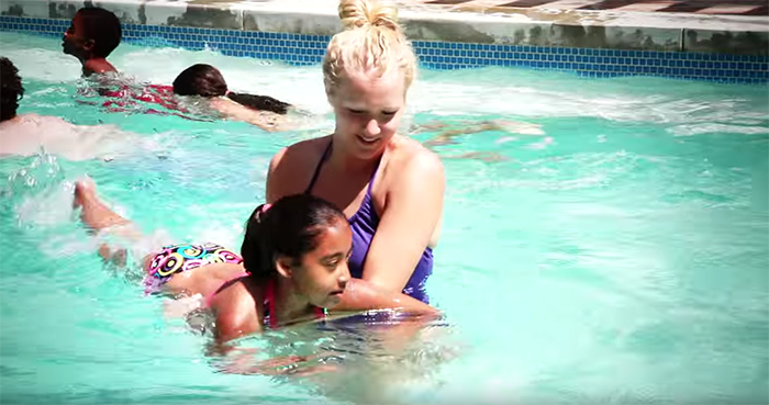 Woman teaching girl to swim