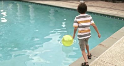 Boy looking at a ball in the pool