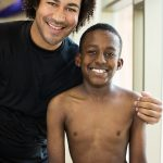 closeup of a man with his arm around a kid and both are smiling.