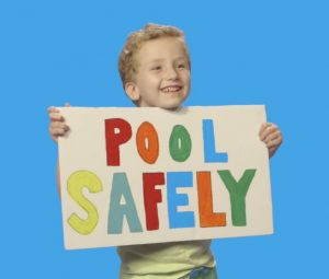 Boy holding a pool safely sign
