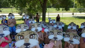 a group of kids outside holding otter masks on their faces.
