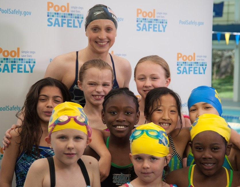 Katie Ledecky with a group of young swimmers.