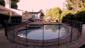 a fence surrounding an in ground pool.