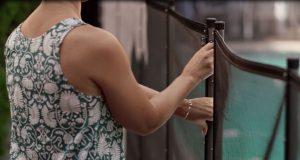 closeup of a woman adjusting pool fencing.