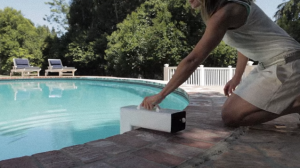 woman kneeling installing a pool alarm.