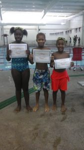 three children holding certificates in front of an indoor pool.