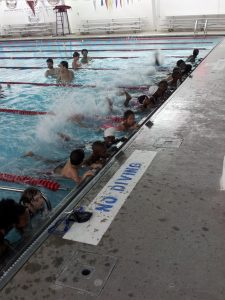 a group of children holding the side of a pool wall and kicking their feet making splashes.