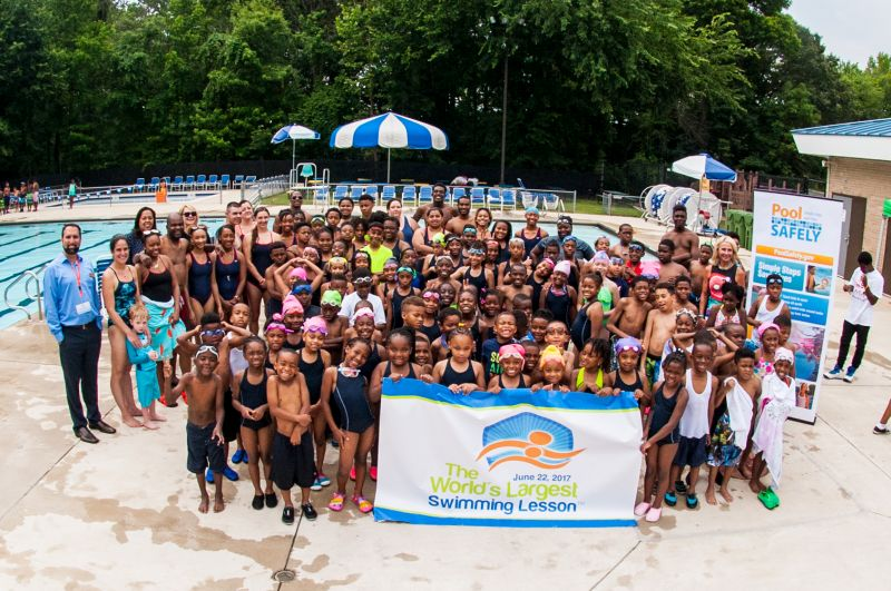 "A group of kids in front of a sign stating ""the worlds largest swimming lesson"""
