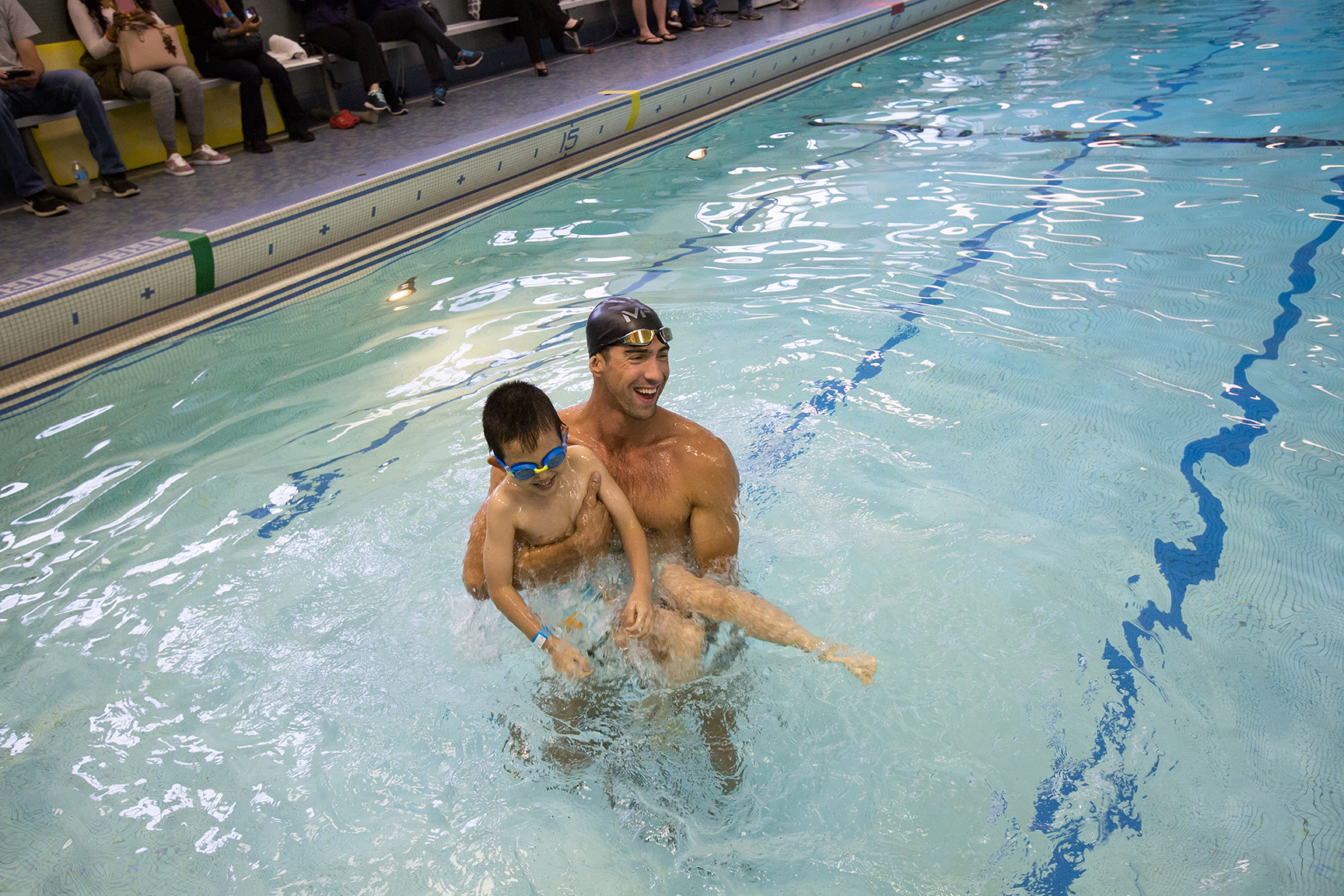 Michael Phelps in the pool holding a boy