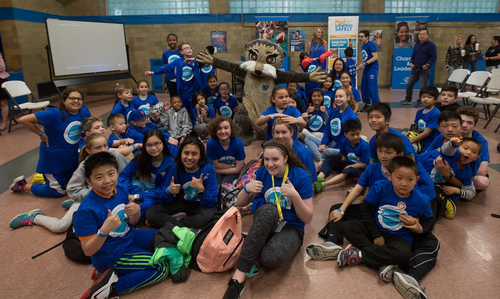 a group of kids in blue shirts posing with a person in an otter costume.