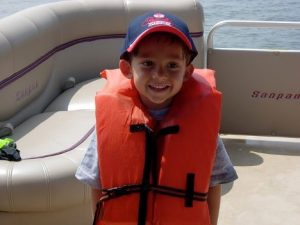 a young boy on a boat wearing a life vest.