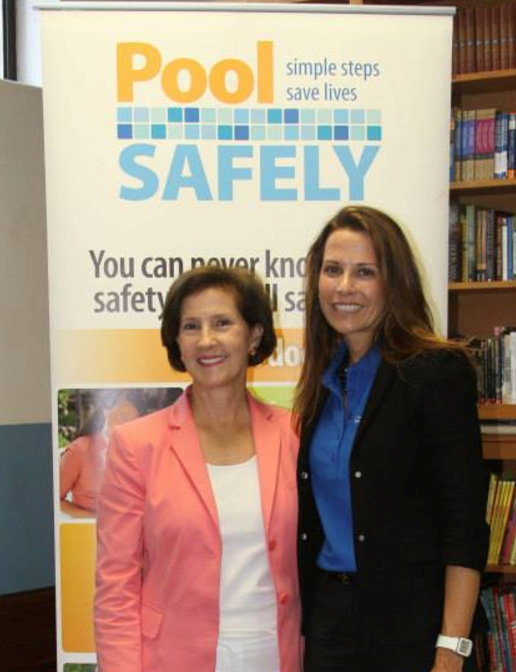 two women standing in front of a big pool safely banner.