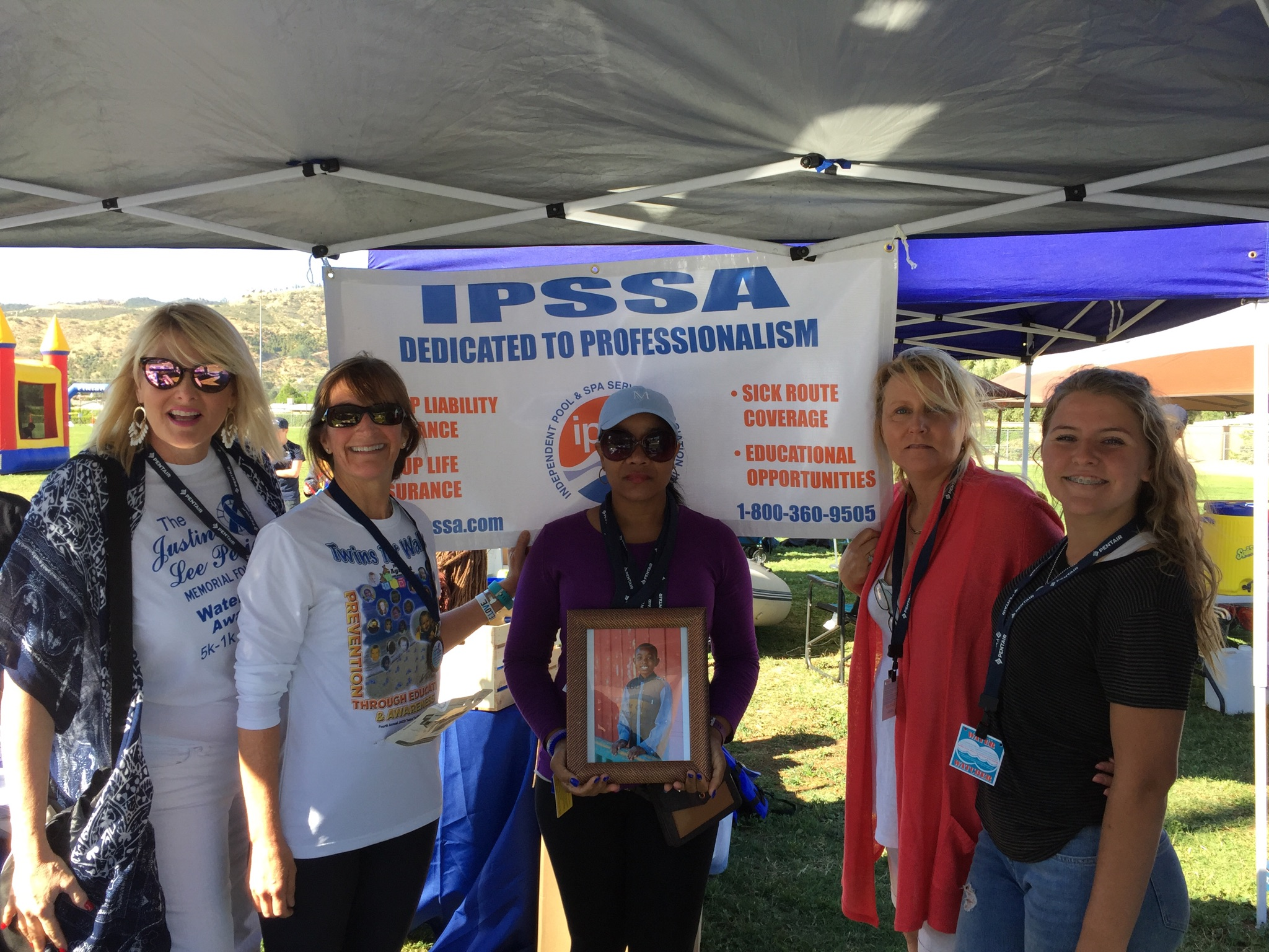 group of women standing in front of an i.p.s.s.a banner with a photograph of a young boy.