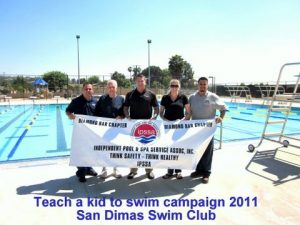 a group of 5 people holding a banner in front of a pool.