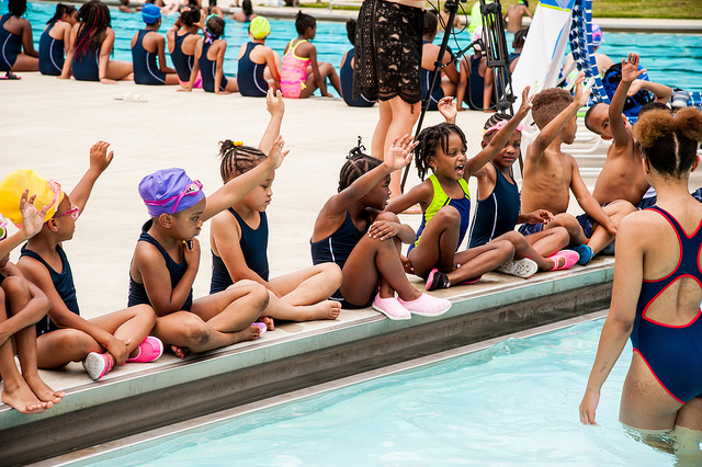 a group of children sitting on the side of a pool raising their hands.