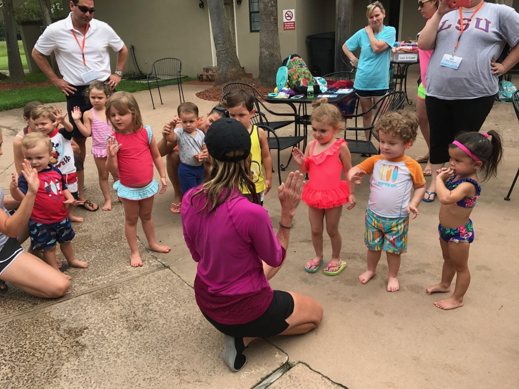 a group of very young children standing around a woman crouched down with her hand raised.