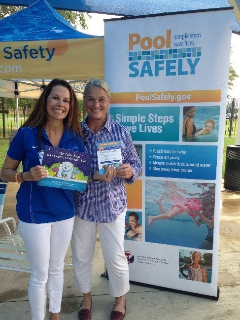 two women smiling and standing in front of a pool safely sign.