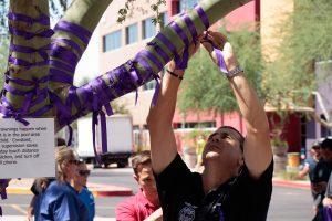Man putting purple ribbon on a tree