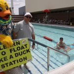 a person in a duck costume standing with a man next to a pool where a lifeguard is helping a girl to float.