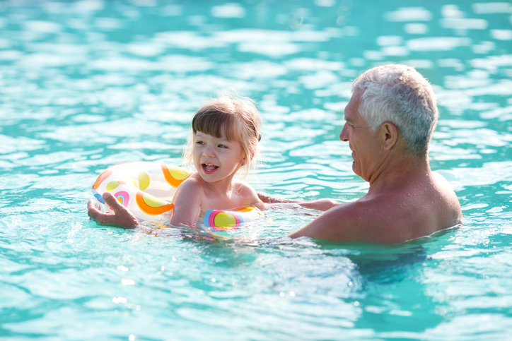 Grandfather and granddaughter swimming in the pool.