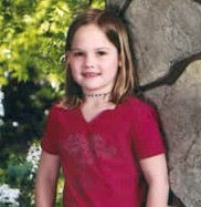 a school photo of a young girl wearing a red shirt.