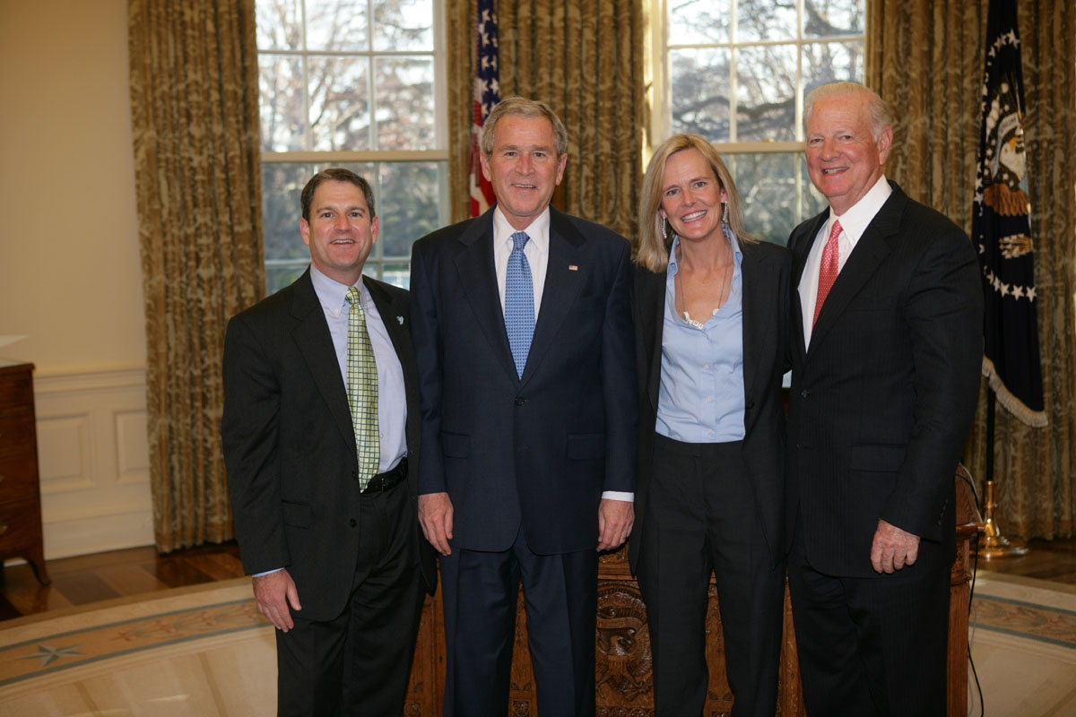 three men and one woman standing in the oval office.