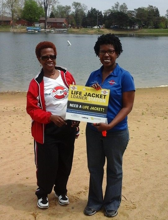 two women standing in front of a lake with a sign.
