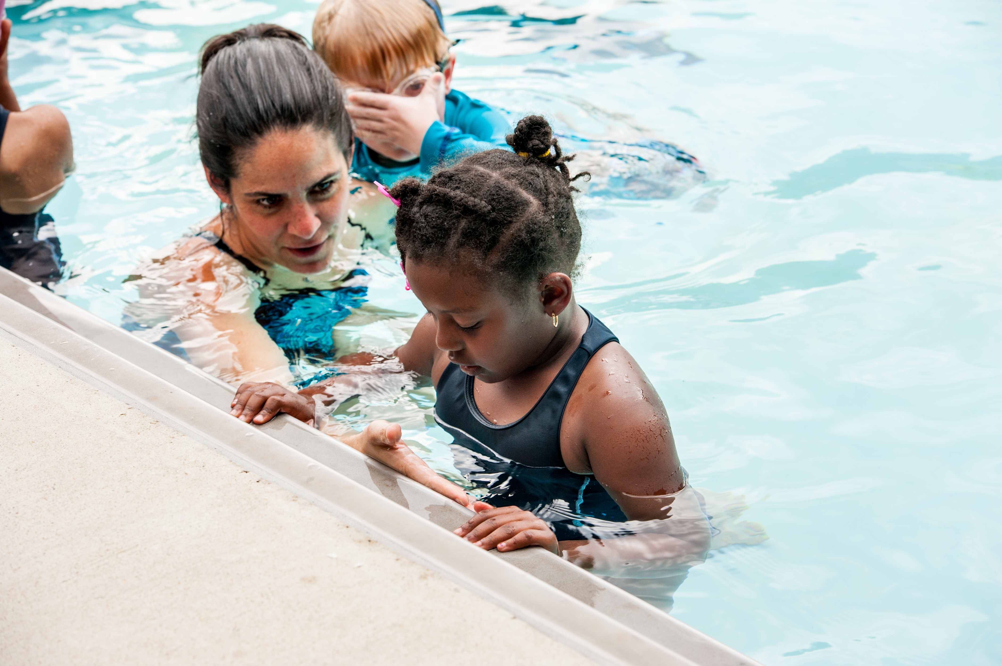 an adult woman talking to a child who is holding onto the side of the pool.