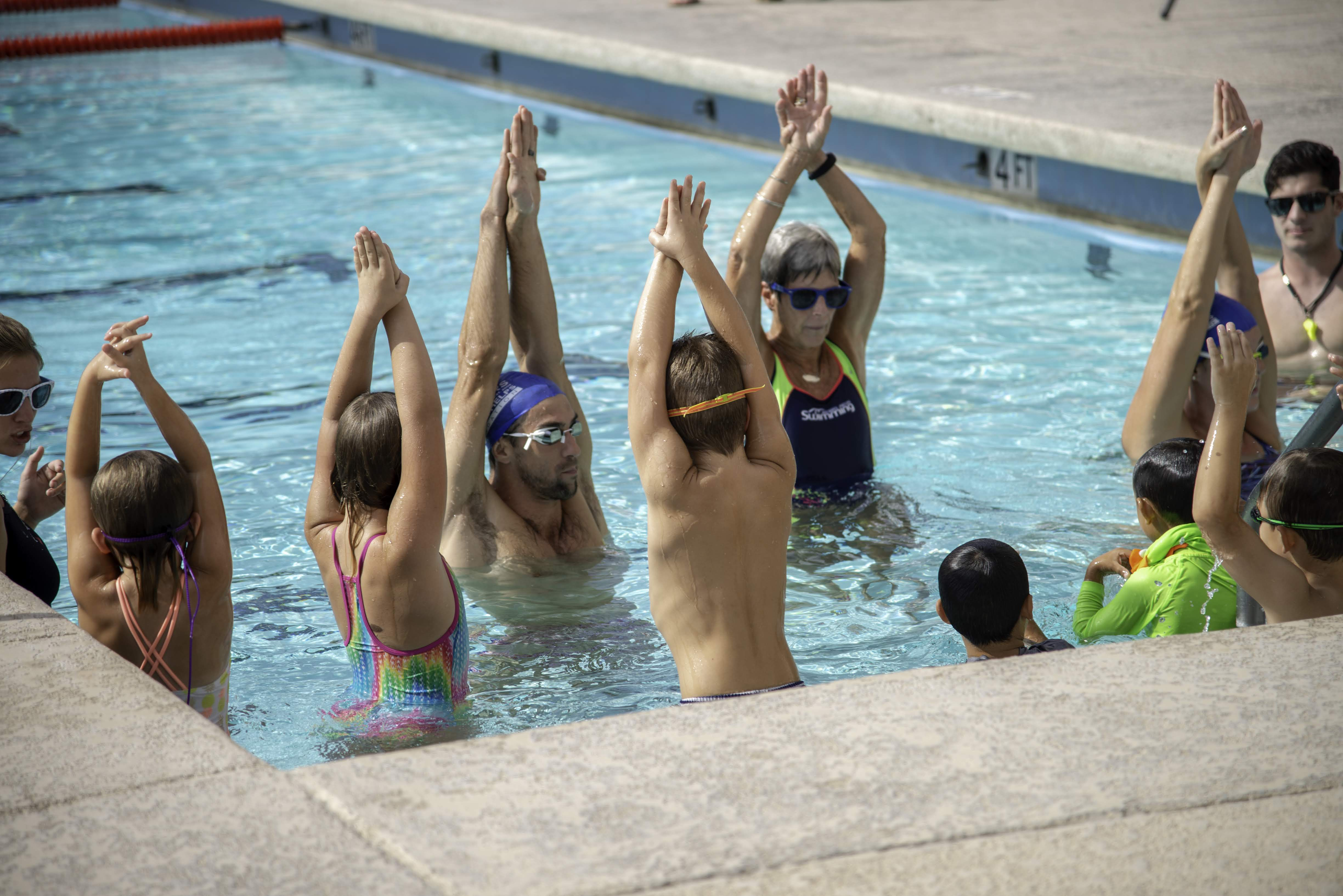 a group of kids in a pool with their hands raised above their heads.