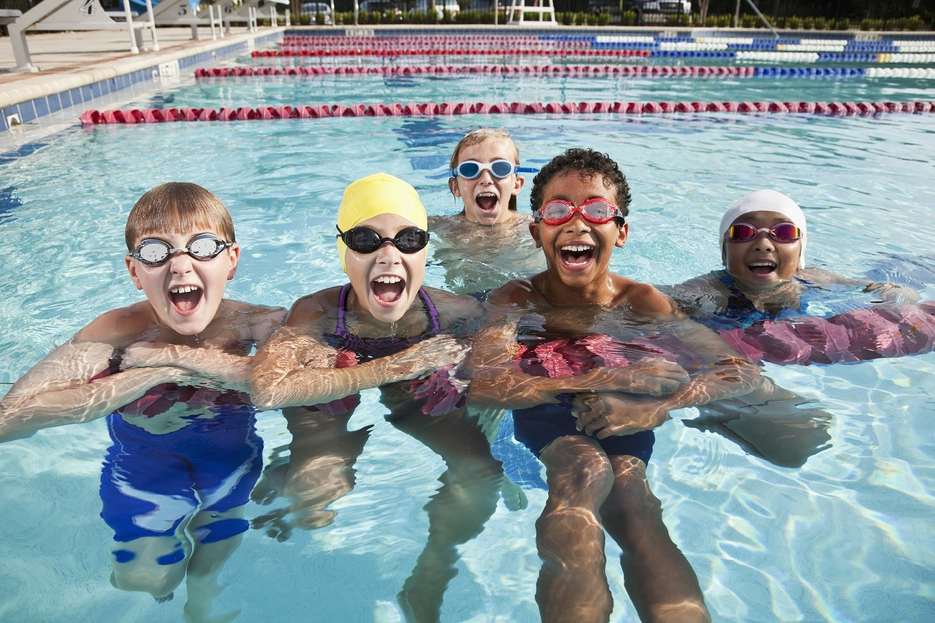 Group of children having fun in swimming pool. Ages 9 to 12 years.