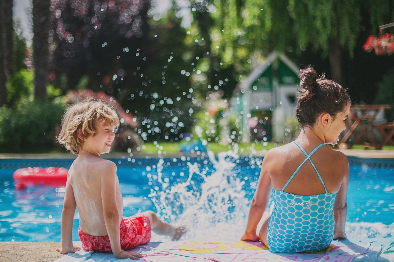 two kids having fun splashing water in poolside.