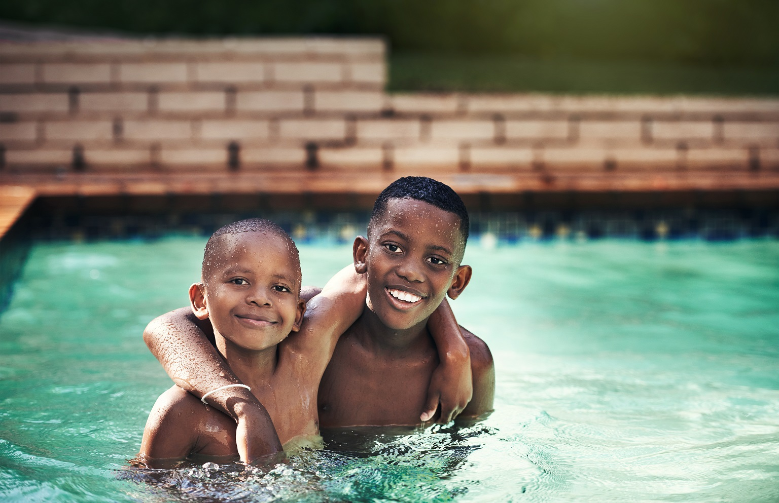 Shot of two young boys having fun together in a swimming pool.
