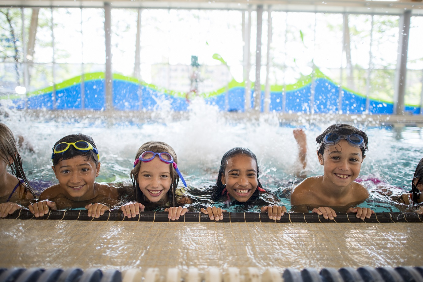 A multi-ethnic group of elementary school children are indoors in a fitness center. They are wearing swimming suits and goggles during swimming class. They are kicking at the side of the pool to practice.