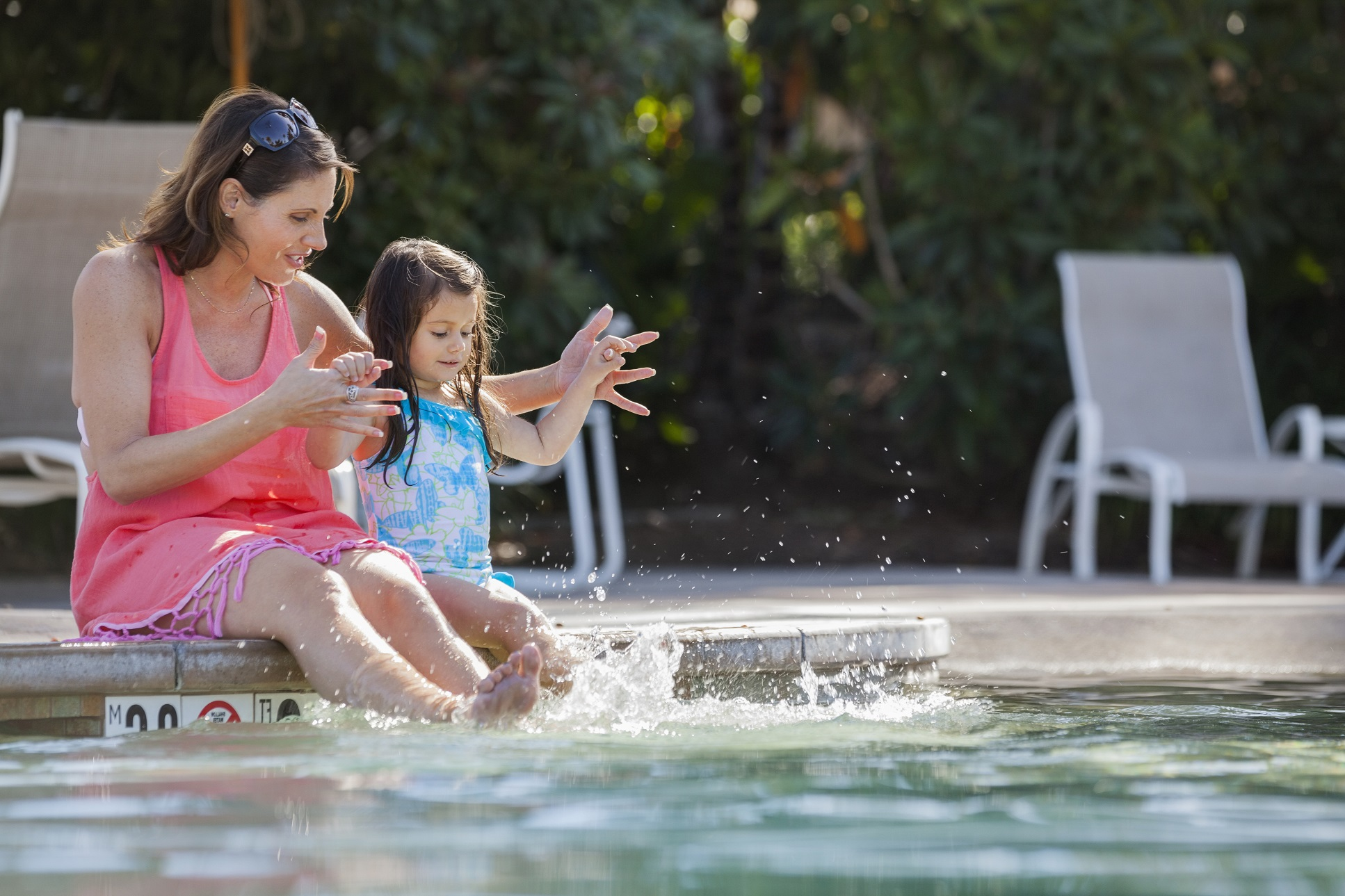 Mother and daughter sitting at the edge of pool splashing