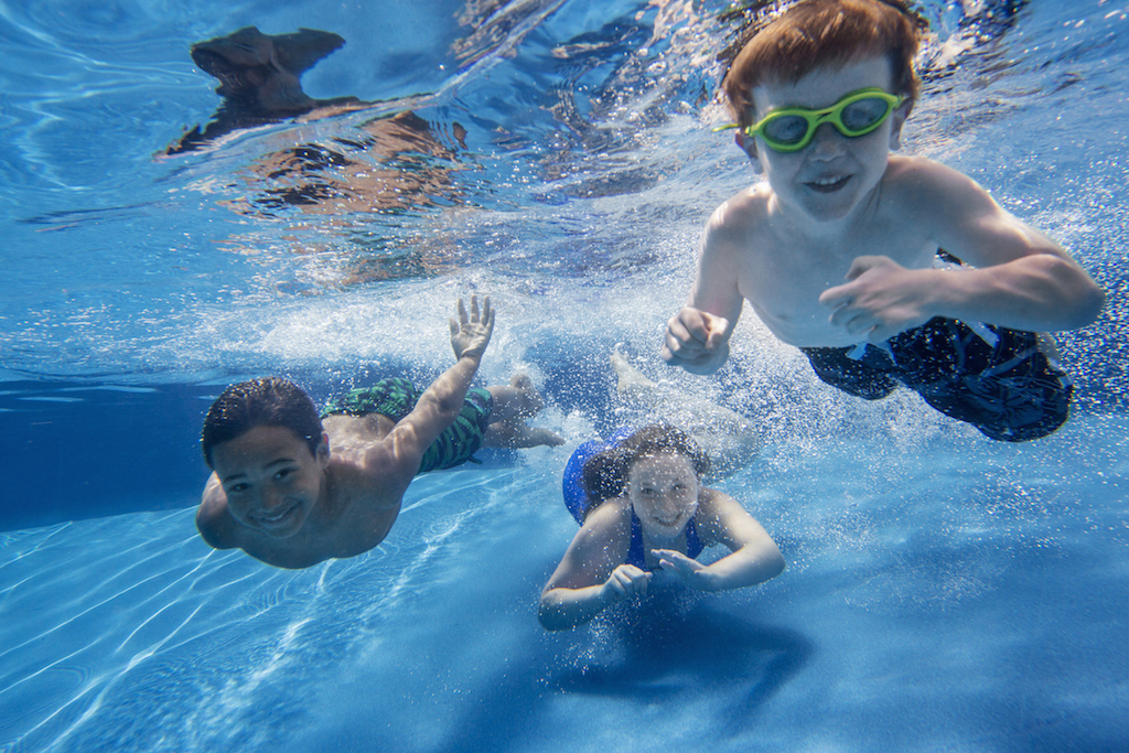 Three children swimming underwater, smiling at the camera.