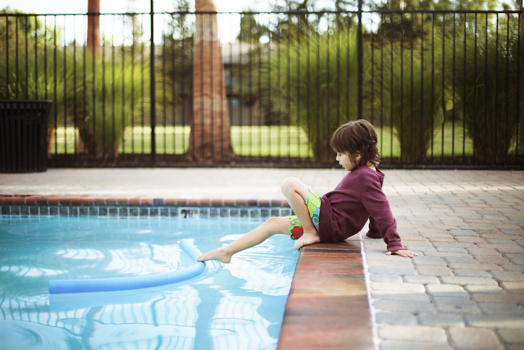 Boy playing with noodle float while sitting poolside
