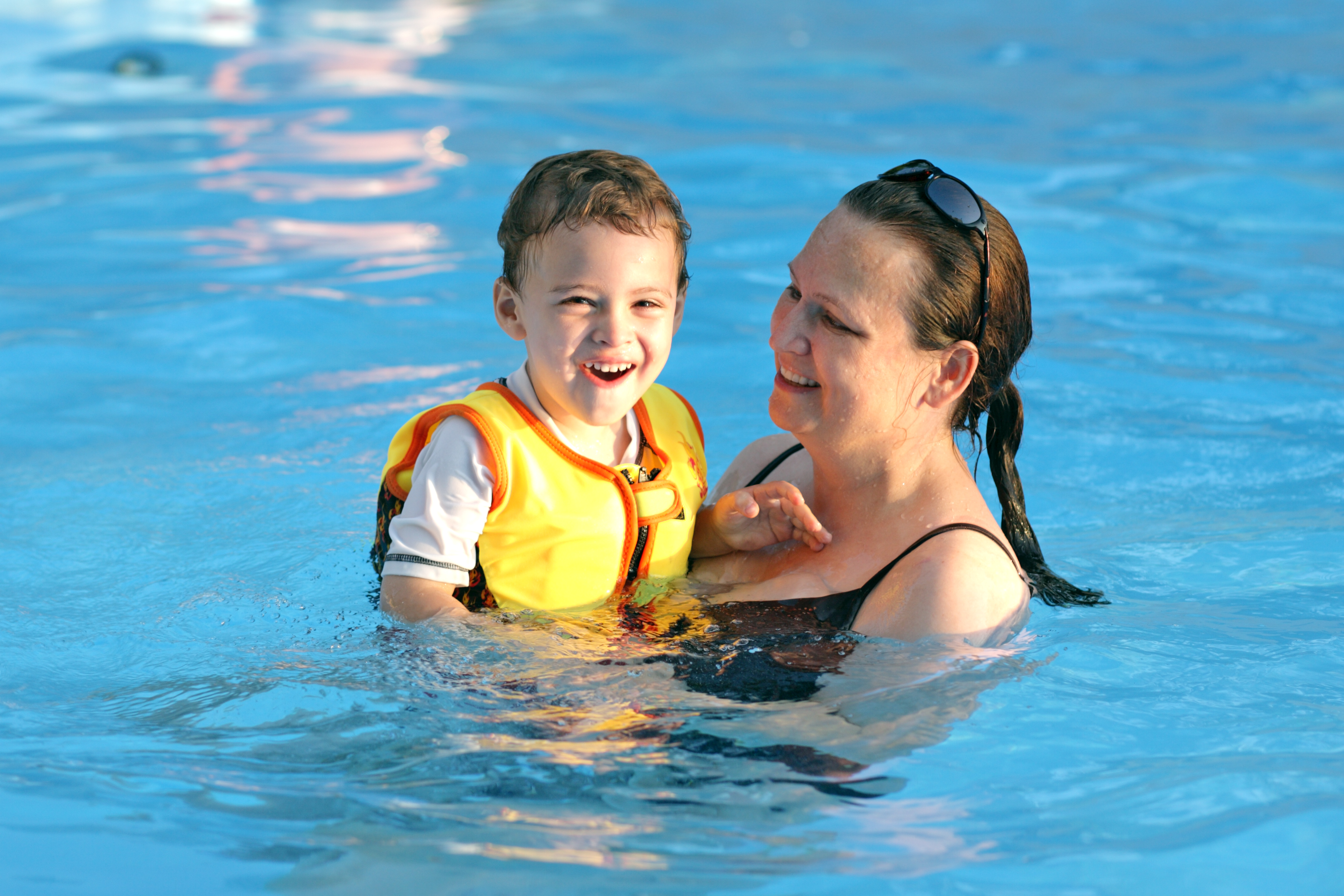 Mom swimming with autistic son