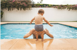 a child on the side of a pool ready to jump into a man's arms.