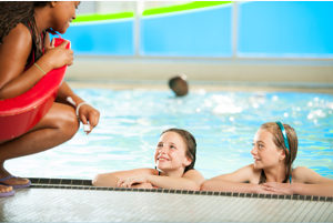 two kids in a pool looking up at an instructor.