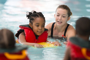 a child wearing a life vest with an adult in a pool.