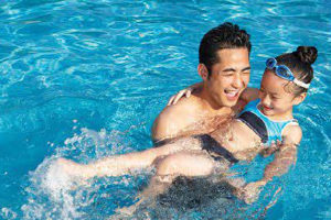 a father swimming with his daughter in the pool.