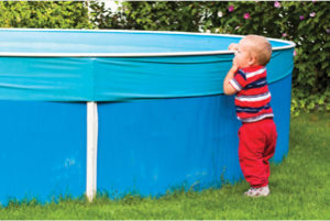 a child looking over the side of an above ground pool.