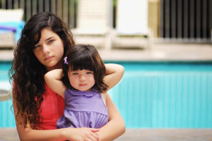 a young adult and child next to a pool.